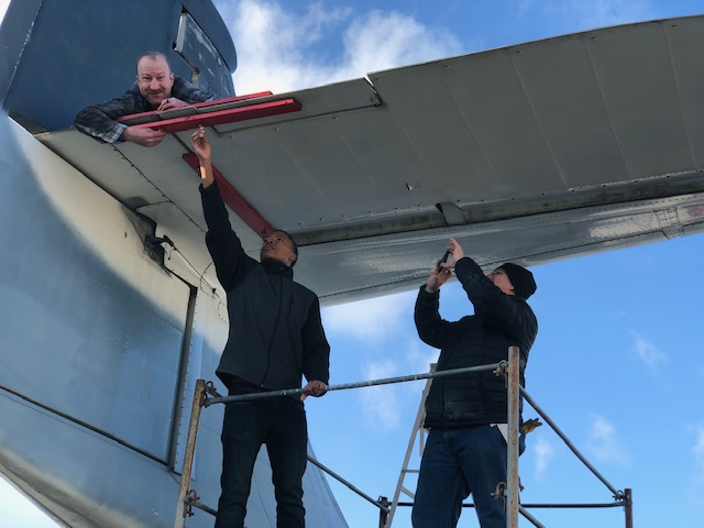 Three individuals working on aircraft gust locks