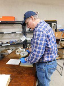 John Hughes examining a vintage ship's chronometer